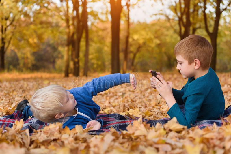 Two little brothers take pictures of each other, lying in yellow autumn leaves. Fall day royalty free stock photography
