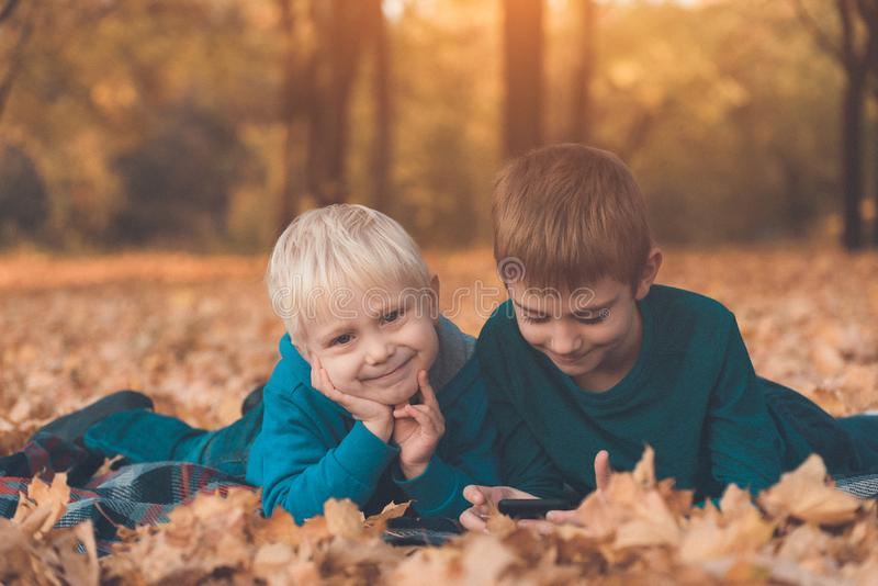 Two little brothers using smartphone, lying in yellow autumn leaves. Smiling and having fun. Fall day.  royalty free stock image