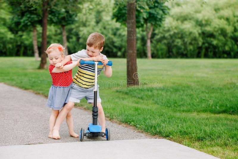 Two little Caucasian preschool children fighting in park outside. Boy and girl can not share one scooter. stock photos