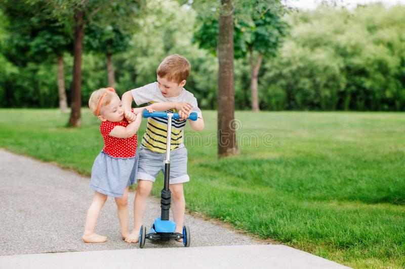 Two little Caucasian preschool children fighting in park outside. Boy and girl can not share one scooter. royalty free stock photos