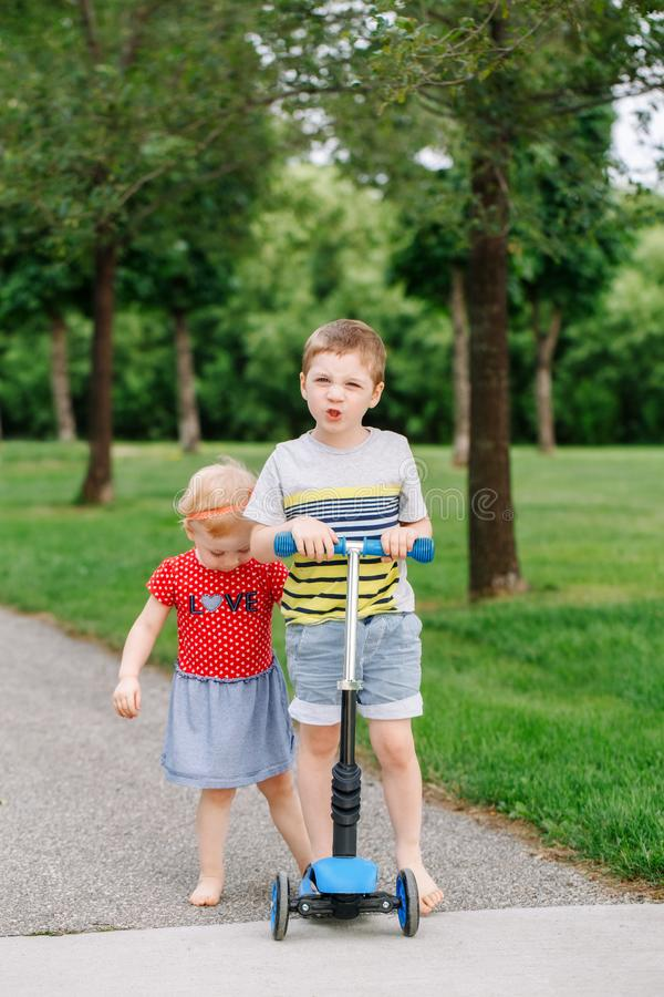 Two little Caucasian preschool children fighting in park outside. Boy and girl can not share one scooter. stock photo