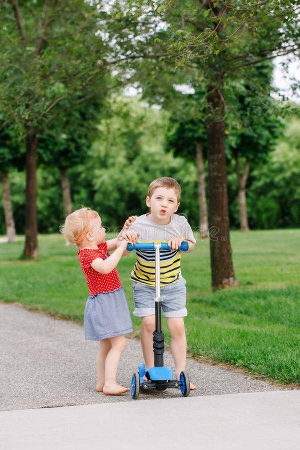 Two little Caucasian preschool children fighting in park outside. Boy and girl can not share one scooter. royalty free stock image
