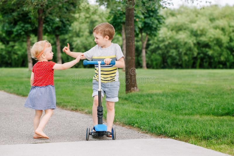 Two little Caucasian preschool children fighting in park outside. Boy and girl can not share one scooter. stock images