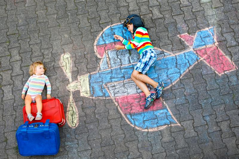 Two little children, kid boy and toddler girl having fun with with airplane picture drawing with colorful chalks on stock photo