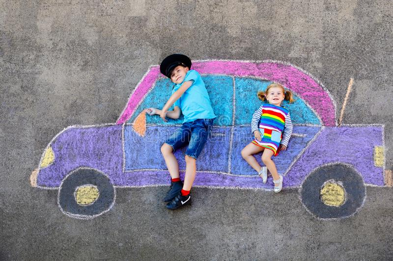 Two little children, kid boy and toddler girl having fun with with car picture drawing with colorful chalks on asphalt. Siblings painting on ground and playing stock photography