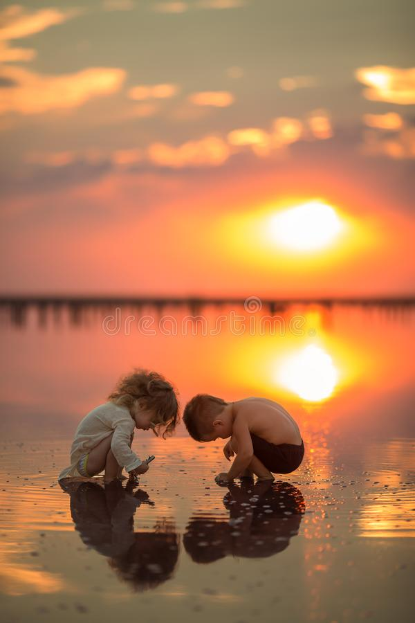 Two little children playing on the beach during sunset. Reflection in water stock image