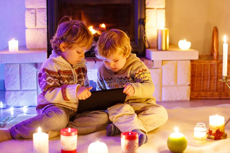 Two little children sitting by a fireplace at home on Christmas time. Happy cute adorable toddler boys, blond twins stock images