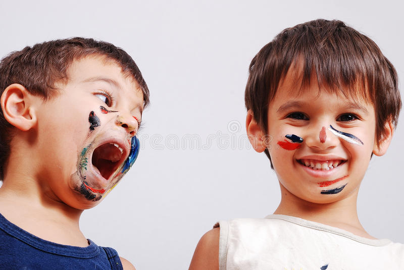 Two little cute brothers with colors on their face stock images