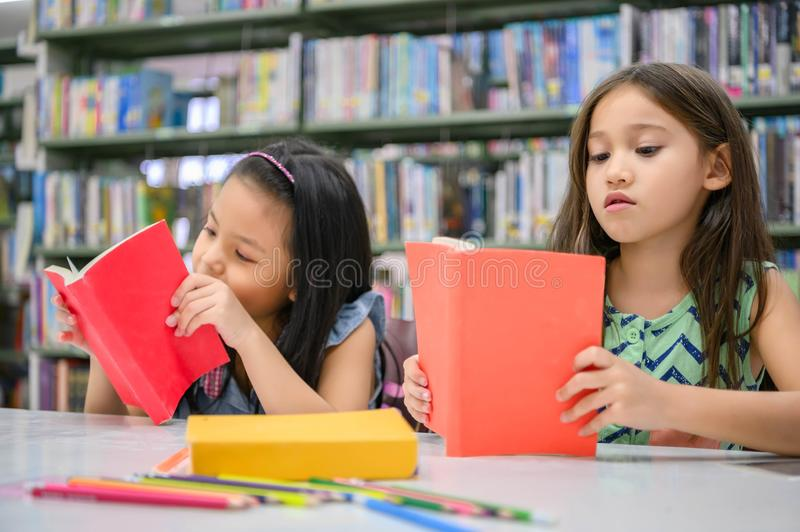 Two little cute girls multi-ethnic friends reading books together in school library. People lifestyles and Education learning stock photo