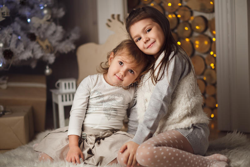 Two little cute girls sitting near christmas tree and fireplace royalty free stock photos