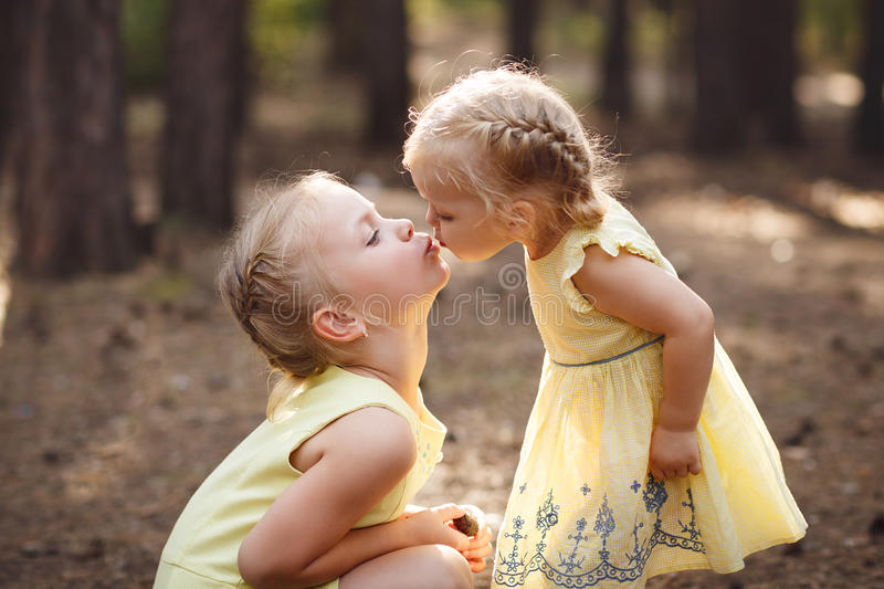 Two Little Cute Sisters In Yellow Dresses Are Kissing In The Par Stock Photo - Image -4415