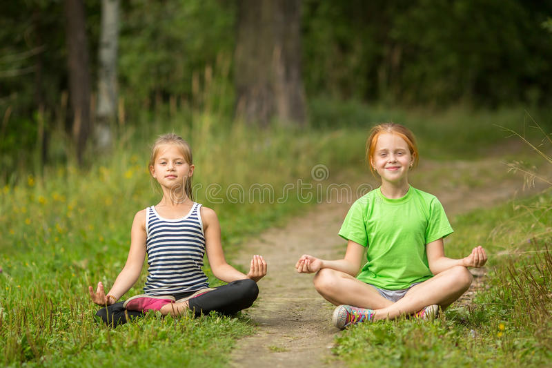 Two little cute yoga girls sitting in Lotus position. Outdoors stock images
