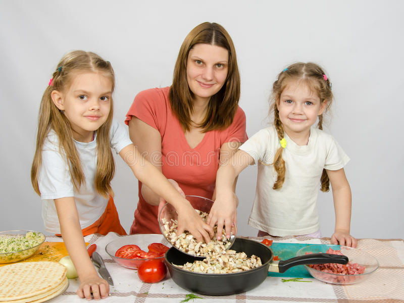 Two little daughter at kitchen table helping her mother pour chopped mushrooms from the plate to the pan royalty free stock images