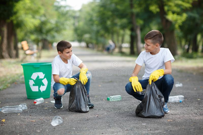 Two little ecologists sitting and collecting plastic rubbish on a blurred park background. Ecology protection concept. stock photography