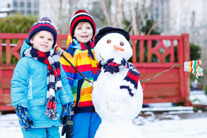 Two little friends making a snowman, playing and having fun with royalty free stock photo