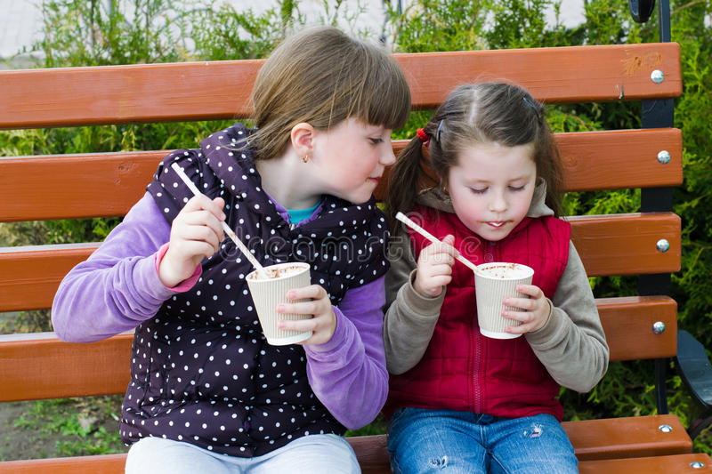 Two little funny girl on a park bench stock images