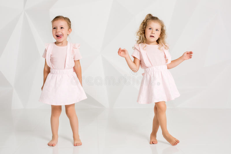 Two little funny and laughing girl in gently pink dresses posing in white studio royalty free stock photos