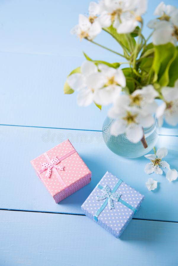 Two little gift boxes with beautiful bouquet of white flowers of blooming cherry branches on blue wooden background. royalty free stock photography