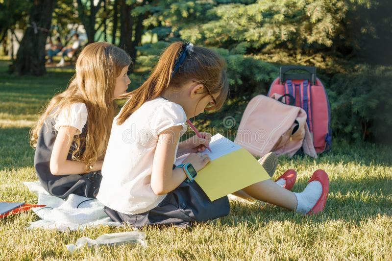 Two little girl friends schoolgirl learning sitting on a meadow in the park. Children with backpacks, books, notebooks. View from stock photos