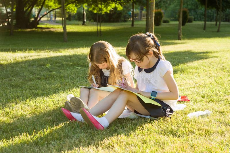 Two little girl friends schoolgirl learns sitting on a meadow in the park. Children with backpacks, books, notebooks. View from th royalty free stock photos