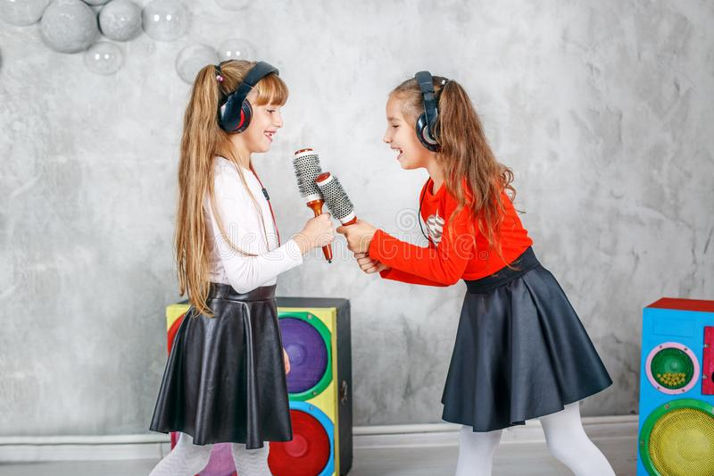 Two little girl friends sing and dance. The concept is childhood royalty free stock photos