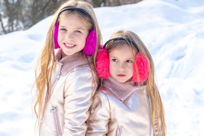 Two little Girl playing with snow in park. Winter kids portrait. Two adorable young girls having fun together in royalty free stock images