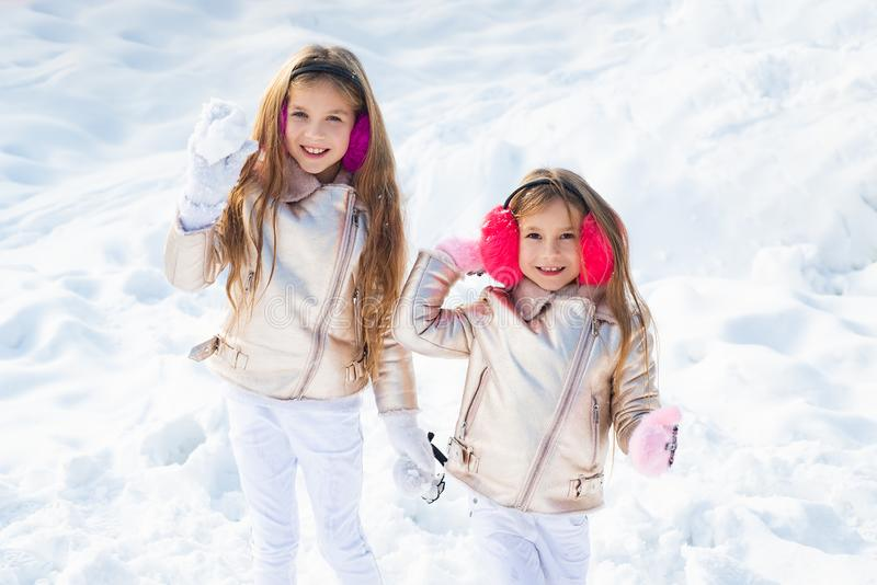 Two little girl playing on snow in winter time. Snowball fight. Winter kids having fun playing in snow outdoors. Kids. Throwing a snowball stock image