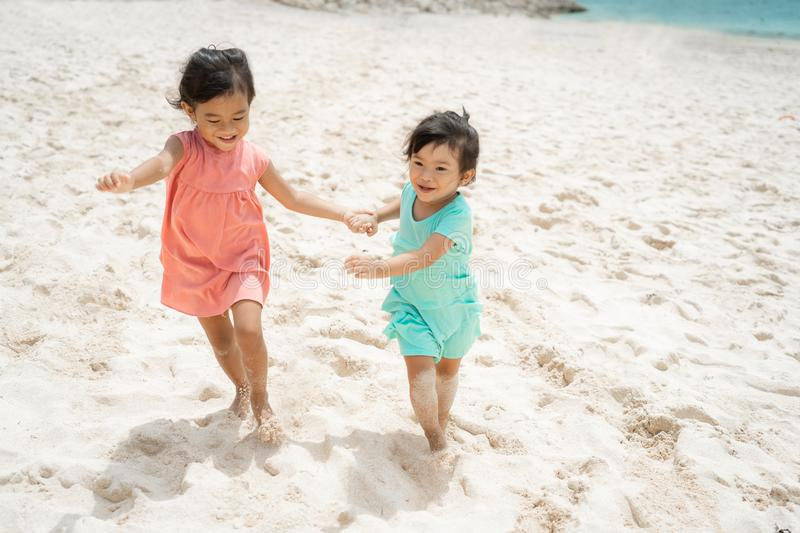 Two little girl running with hold hand enjoy playing together stock image