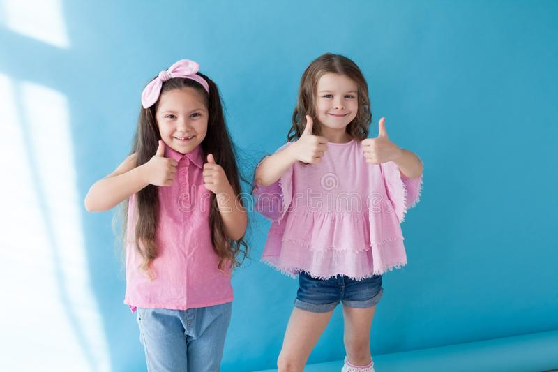 Two little girl shows hands symbol thumb up royalty free stock photos