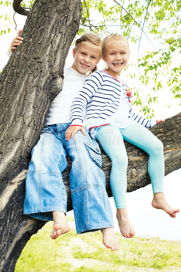 Two little girl sitting on a tree and waving her bare fee royalty free stock photos