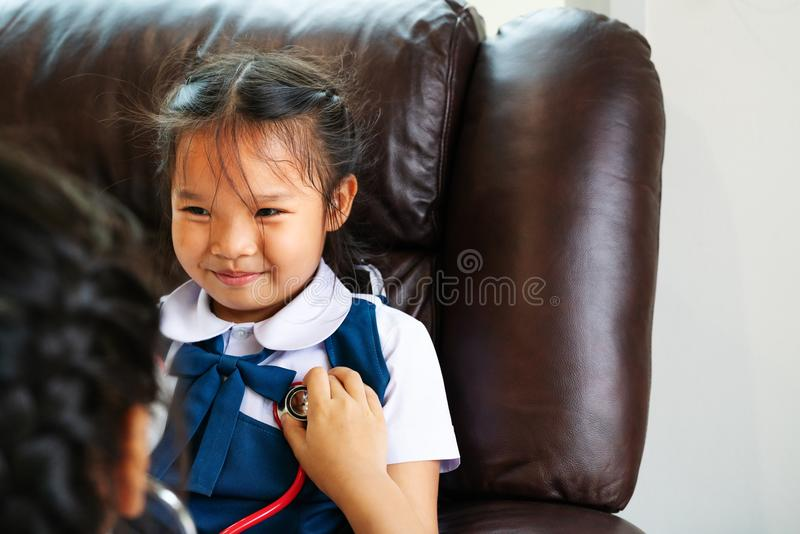 Two little girl are smiling and playing doctor with stethoscope. Kid and health care concept. stock images