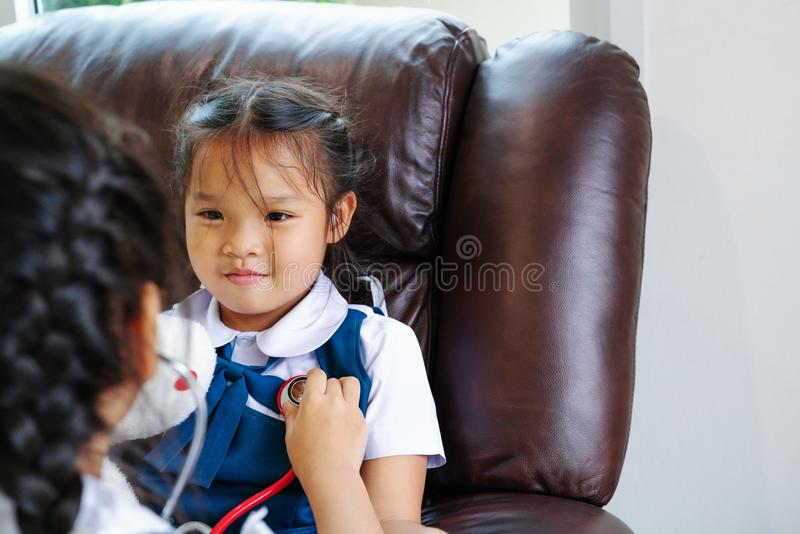 Two little girl are smiling and playing doctor with stethoscope. Kid and health care concept. stock image