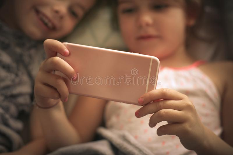 Using smart phone in bed. Two little girl using smart phone together. Close up. Focus is on hands stock photos