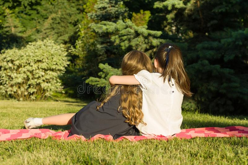 Two little girlfriends embracing sitting on a meadow in the park. View from the back royalty free stock image