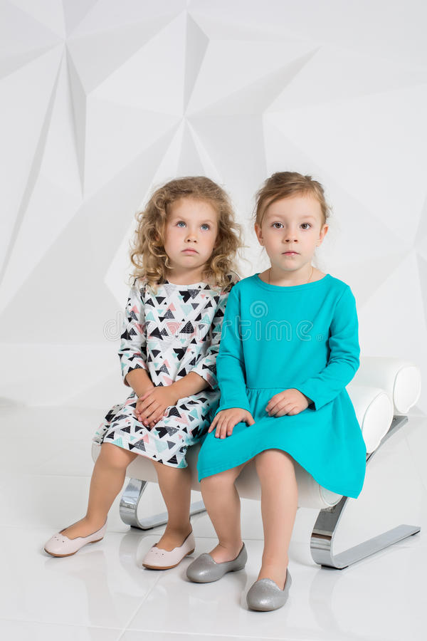 Two little girlfriends in the identical dresses of different colors sitting on a chair in a studio with white walls royalty free stock images