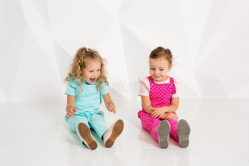 Two little girlfriends in the identical overalls of different colors sitting on the floor in a studio with white walls stock images
