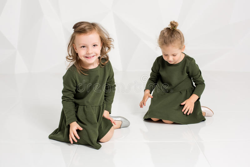 Two little girlfriends in the same dark green dresses sitting on the floor in a studio with white walls royalty free stock image