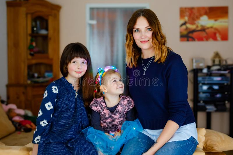 Two little girls, adorable little toddler and schoolgirl with beautiful young mother. Happy healthy family portrait, mom stock photo