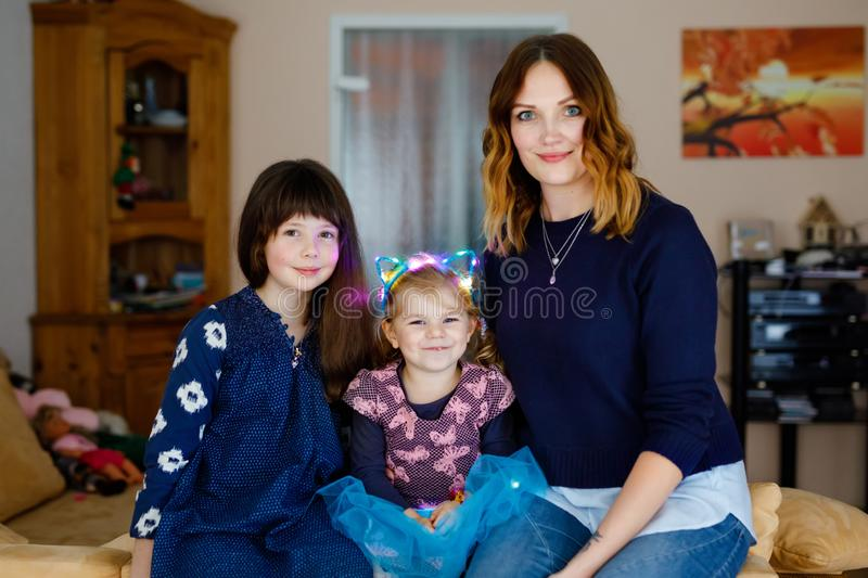 Two little girls, adorable little toddler and schoolgirl with beautiful young mother. Happy healthy family portrait, mom royalty free stock photo