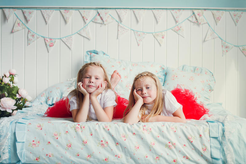 Two little girls on the bed stock images