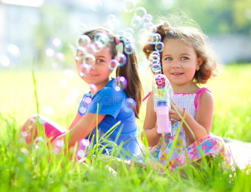 Two little girls are blowing soap bubbles. Outdoor shoot stock photos