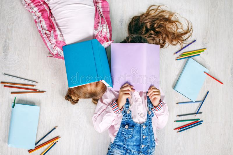 Two little girls with books. Flat lay. The concept of childhood, learning, friendship, family, school, lifestyle. royalty free stock photos