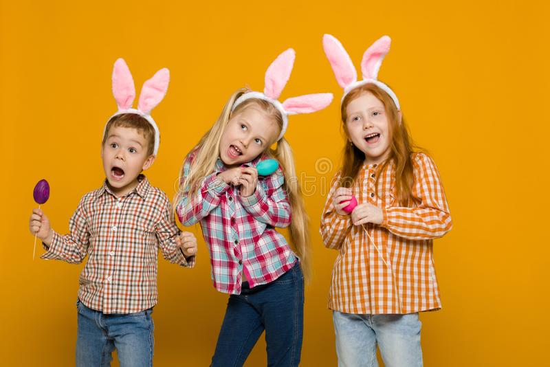 Two little girls and boy with Easter bunny ears holding colorful eggs royalty free stock images