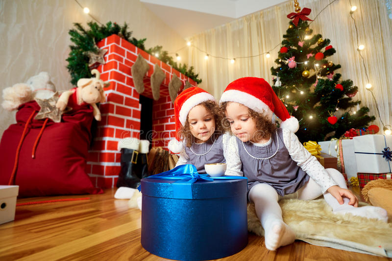 Two little girls in caps of Santa Claus sitting on the floor wit royalty free stock photo
