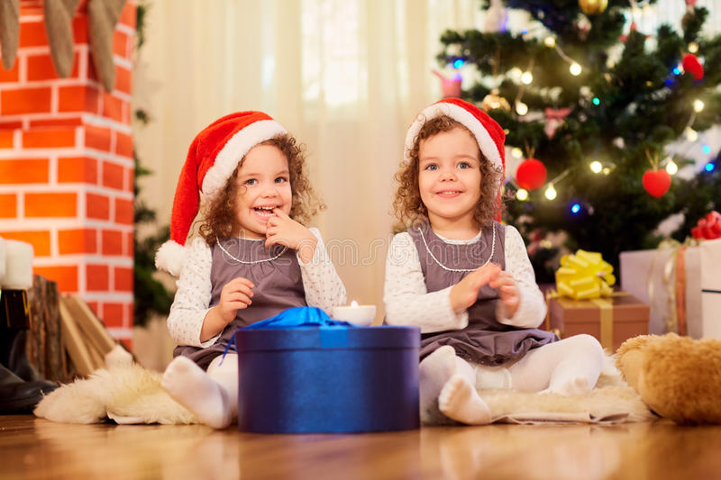 Two little girls in caps of Santa Claus sitting on the floor wit. H gifts in the room with the Christmas tree royalty free stock photos