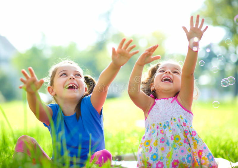 Two little girls are catching soap bubbles stock photos