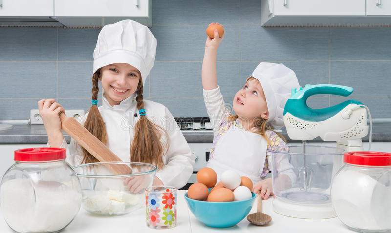 Two little girls in chef uniform with ingredients on table stock photo