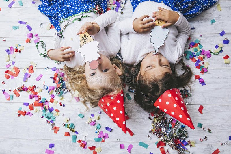 Two little girls child fashion colorful confetti on the floor an royalty free stock image