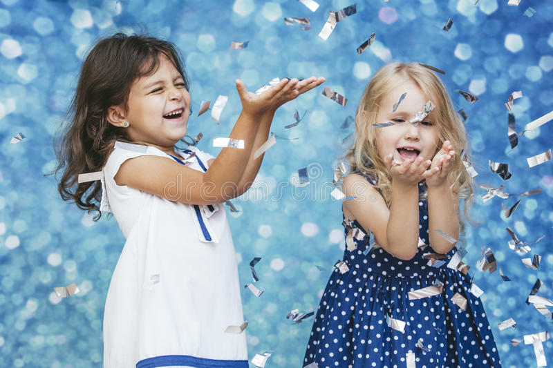 Two little girls child fashion with silver confetti in the background with patches of cute and beautiful stock photography