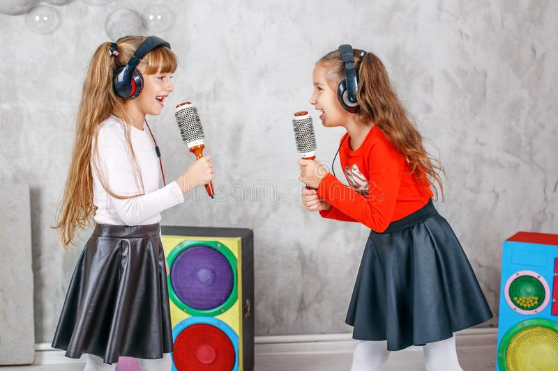 Two little girls the children sing and play. The concept is childhood, lifestyle, dance, music. royalty free stock photo